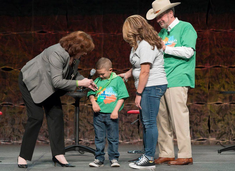 Honored Kid Derryk receives a medal from Kathleen Ruddy