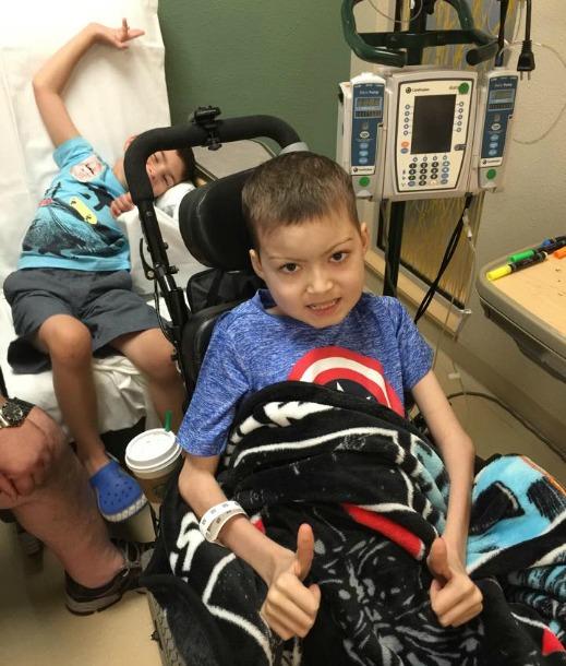 Brayden goofs off behind Julian during a hospital visit