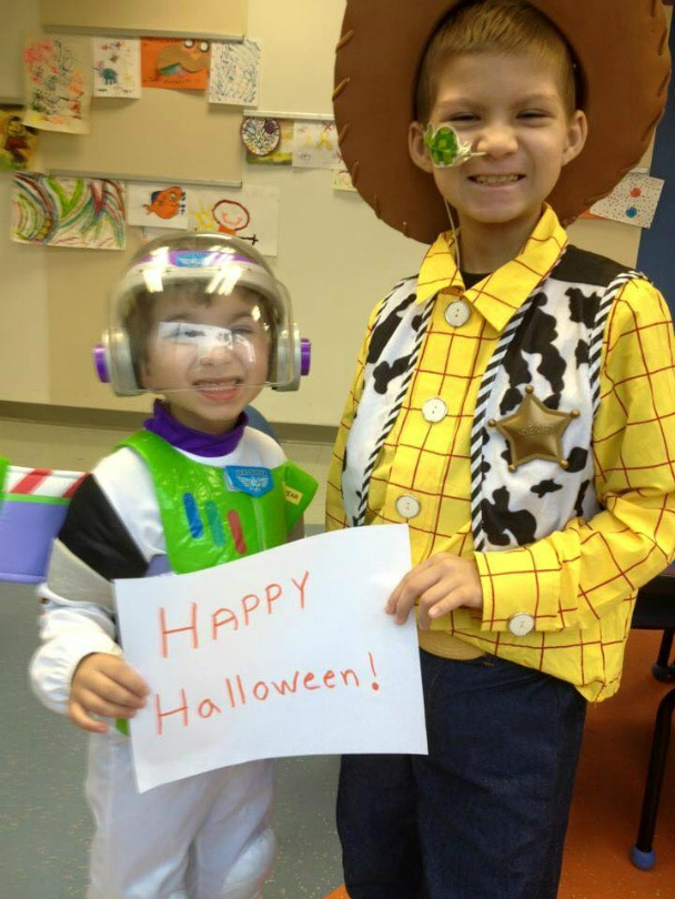 Julian and Brayden, dressed as Buzz Lightyear and Woody, hold a sign that says: Happy Halloween