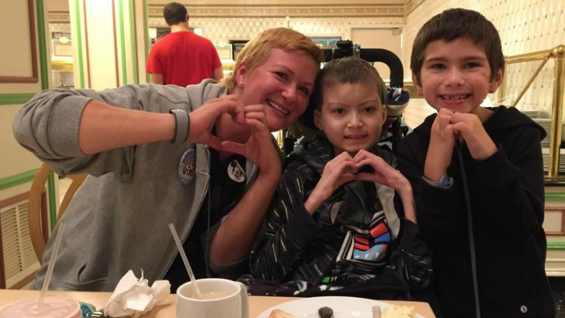 Kristi, Julian, and Brayden make hearts with their hands during Julian's Disney trip