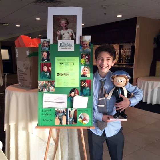 Nathan stands next to his St. Baldrick's poster board at his bar mitzvah