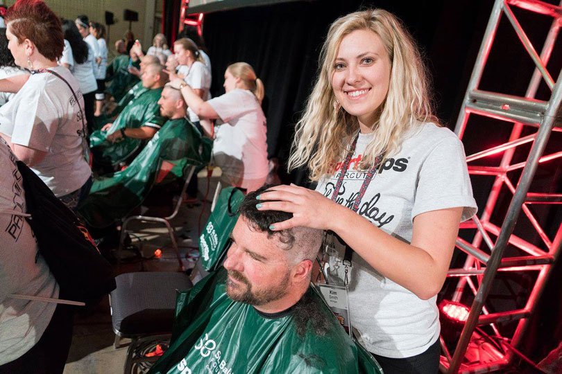 Volunteer barber smiles while shaving a head