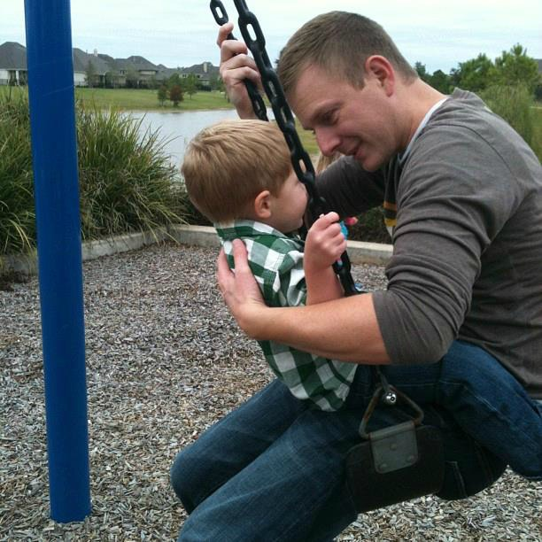 Liam with his dad on a swing