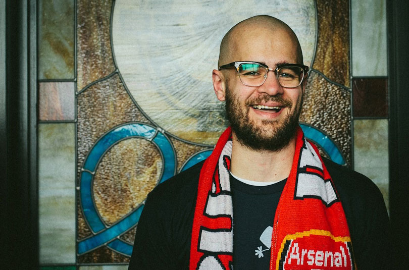 Andrew smiles wearing an Arsenal scarf