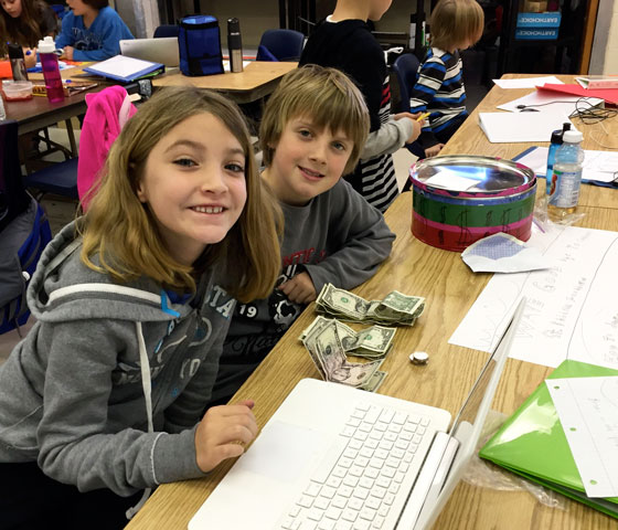two students count money raised daily