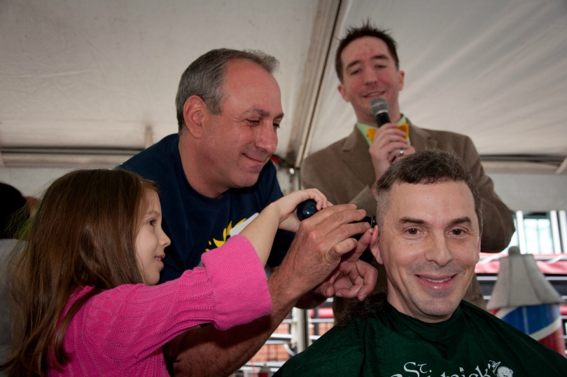 Dr. Dan Wechsler smiles as he gets shaved at a St. Baldrick's event