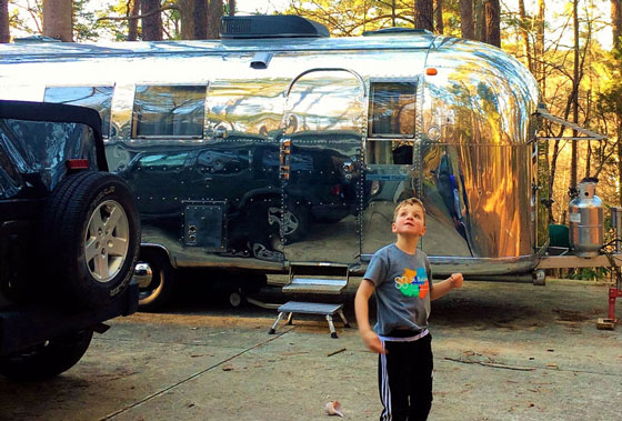 Phineas standing in front of vintage Airstream