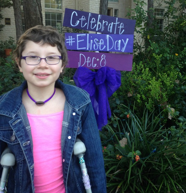 Elise smiles at the camera in front of a sign proclaiming 'Elise Day'