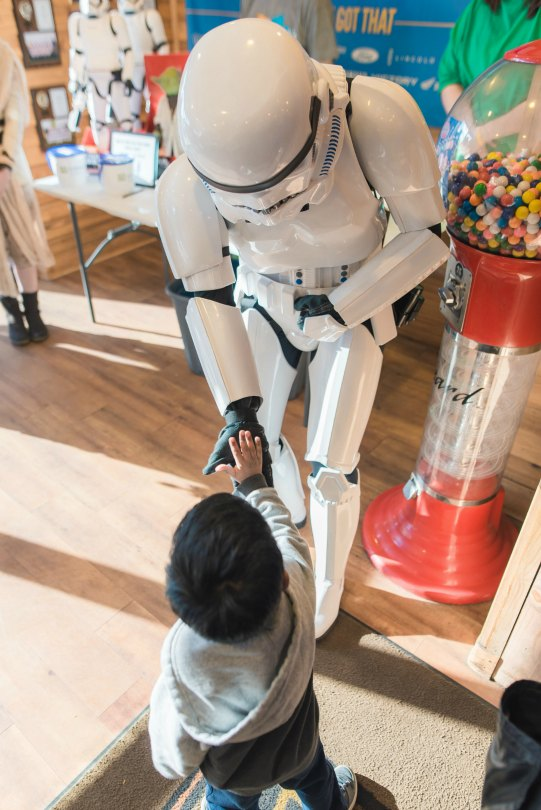 A stormtrooper gives a kid a low-five