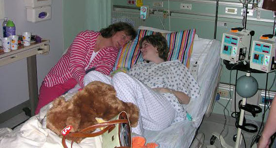 Sarah and her mom laying on her hospital bed