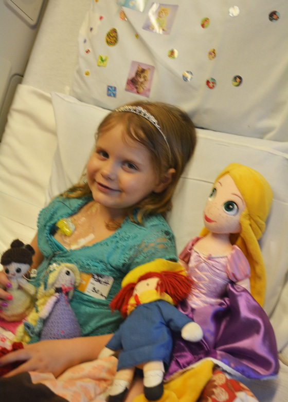 Hazel in her hospital bed surrounded by toys