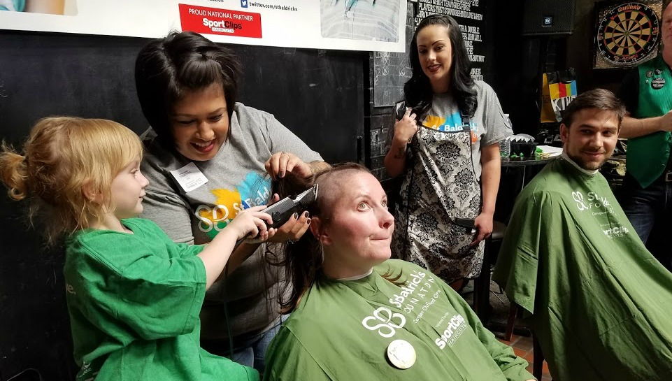 April Prussak helps an Honored Kid shave a head