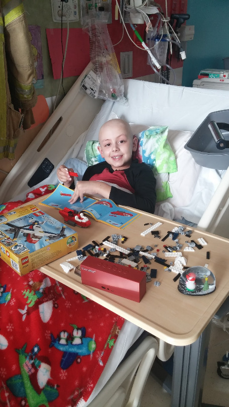 Ori plays with Legos in his hospital bed