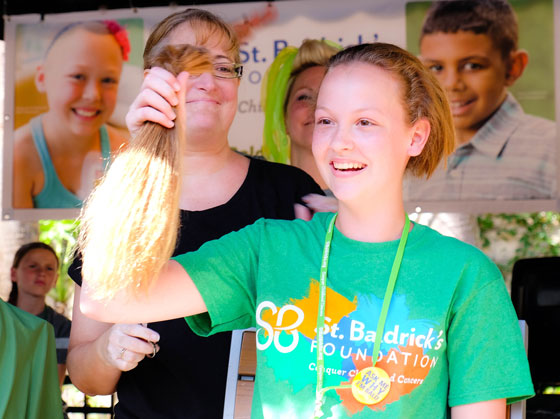 Woman holding a ponytail of hair at a St. Baldrick's event