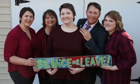 Emily and her family hold a sign that says Be Nice or Leave