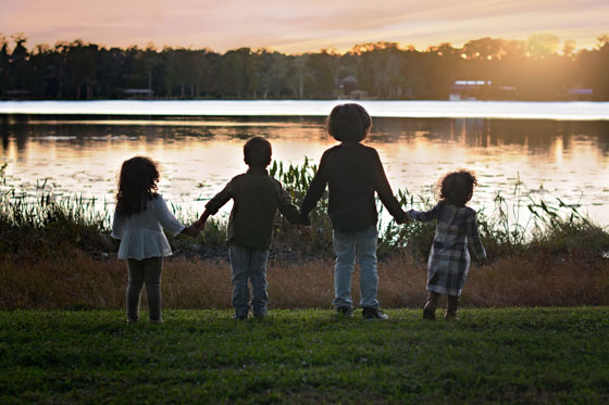 Princeton and his siblings hold hands by the lake
