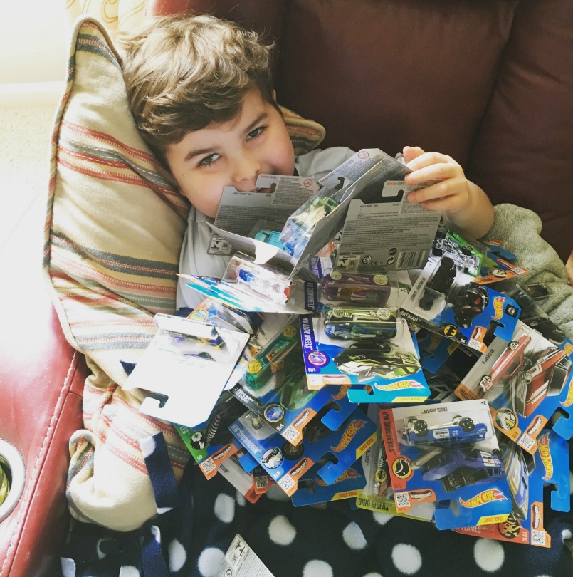 Brooks smiles under a pile of Hot Wheels