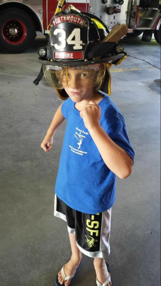 Grayson in a firefighter helmet