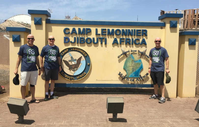 Dr. John York with his fellow shavees in front of the Djibouti sign