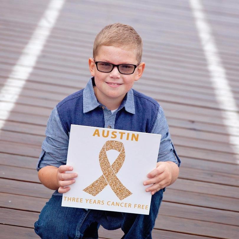 Austin holds a sign that reads: survivor