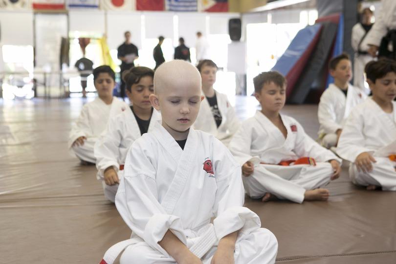 Grace meditates during karate class
