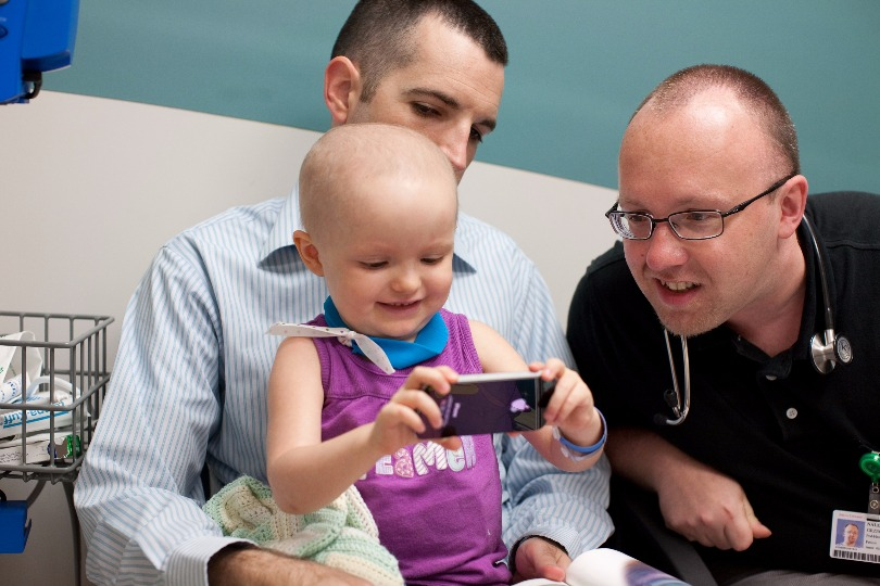 Dr. Nalepa plays on a cellphone with a young patient